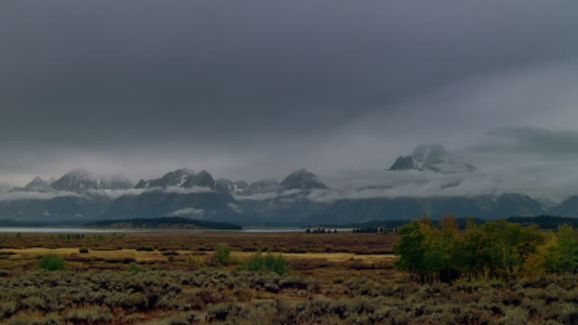 time lapse low clouds moving across grand tetons / sky turning from dark to light / wyoming - grand teton stock videos & royalty-free footage