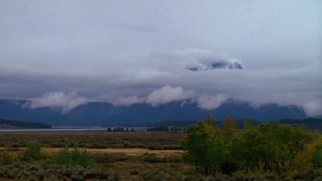 time lapse low clouds moving across grand tetons / yellowstone national park, wyoming - grand teton stock videos & royalty-free footage