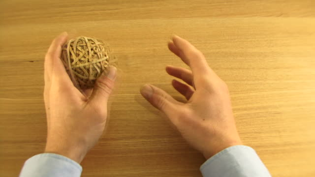 os, ws, time lapse, male playing with ball made of elastic bands on desk - wasting time stock videos & royalty-free footage