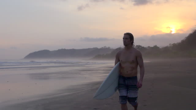 Time Lapse: Man Walking on the Beach after Surfing