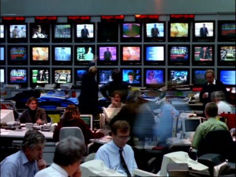 vídeos de stock e filmes b-roll de archival time lapse - mcu people working in television news room, banks of tv screens in background - sala de imprensa