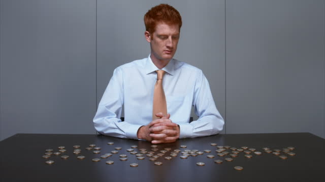 vídeos de stock e filmes b-roll de time lapse medium shot businessman watching coins pile up on table and smiling at cam - empilhar