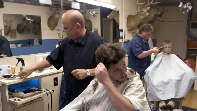 time lapse medium shot lockdown young man getting haircut from barber, boy (9-10) getting haircut in background - hairstyle stock videos and b-roll footage
