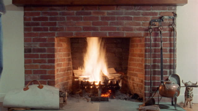 time lapse medium shot man stacking wood in fireplace and lighting fire / fire burning + dying down - anno 2001 video stock e b–roll