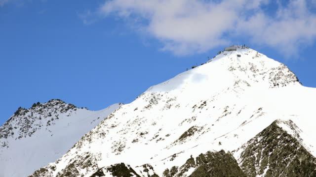 time lapse - medium shot of snowy peaks, passo lucomagno, canton of graubunden, switzerland - wetterstation stock-videos und b-roll-filmmaterial
