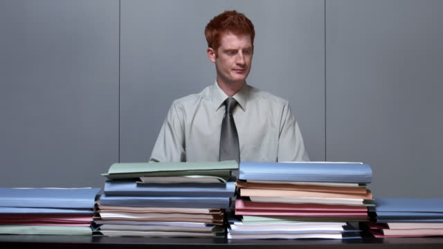 Time lapse medium shot office worker sitting at empty desk with arms crossed / watching folders pile up on desk