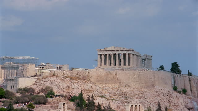 Time lapse medium shot Parthenon / wide shot zoom out Acropolis with clouds moving overhead / Athens, Greece