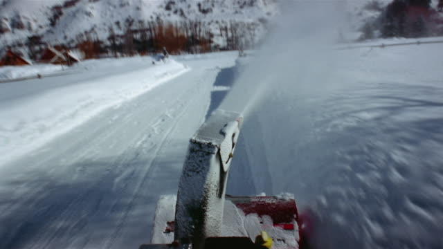 Time lapse medium shot snowblower point of view clearing snow around country house