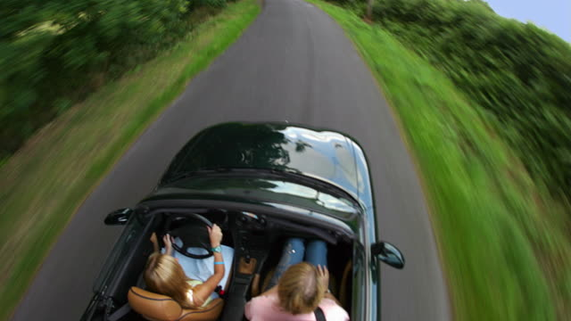 time lapse medium shot tracking shot overhead view of women driving on right side of country road in ingatestone / essex, uk - convertible overhead stock videos & royalty-free footage