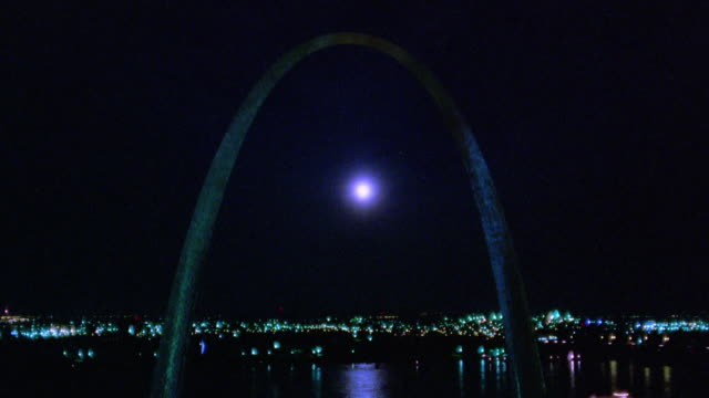 Time lapse moonrise behind Gateway Arch at night with Mississippi River and traffic in background / St. Louis, Missouri