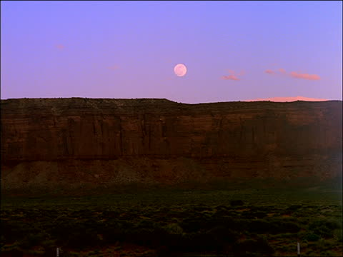 vidéos et rushes de time lapse moonrise, sunset to dusk, over large butte - cinématographie