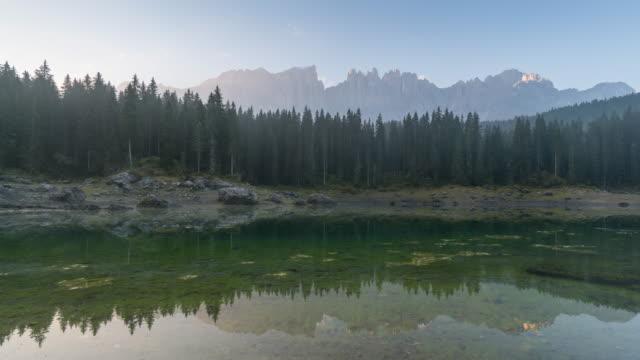 vídeos de stock e filmes b-roll de time lapse mountain with lake, lake of carezza, dolomite, italy - reflection