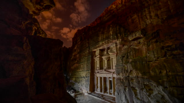 time lapse movie of petra by night, while people lighting candle front of the treasury (al-khazneh), most elaborate temples in the ancient arab nabatean kingdom city of petra - ancient history stock videos & royalty-free footage