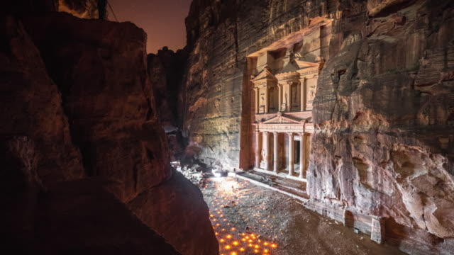 time lapse movie of petra by night, while people lighting candle front of the treasury (al-khazneh), most elaborate temples in the ancient arab nabatean kingdom city of petra - treasury stock videos and b-roll footage