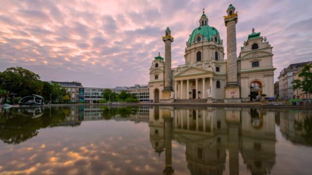 オーストリア、ウィーンのカールスキルシュ教会または聖チャールズ教会の日の出シーンで雲を移動する時間経過 - カールスプラッツ点の映像素材/bロール