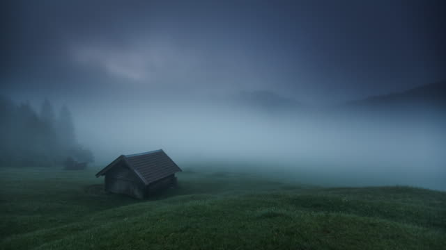 time lapse: mystical fog flowing around cabin in the european alps - european alps stock videos & royalty-free footage