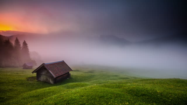 time lapse: mystical fog in the bavarian alps in germany - capanna di legno video stock e b–roll