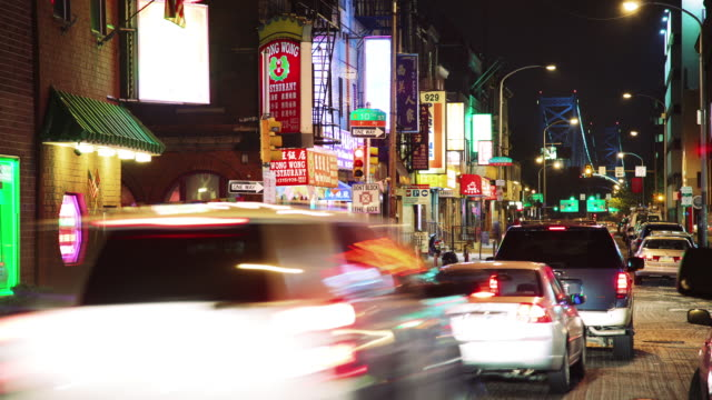 time lapse, night time, inner city, china town with traffic, pedestrians, and shops. - chinatown stock videos and b-roll footage