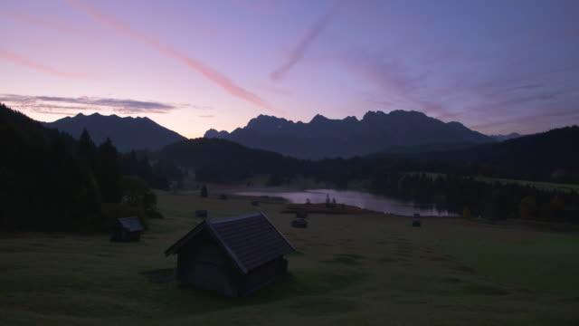 time lapse night to day. lake geroldsee (wagenbrüchsee) with karwendel mountains in background. geroldsee, krün, garmisch-partenkirche, werdenfelser land, karwendel, bavaria, germany. - karwendel mountains stock videos and b-roll footage