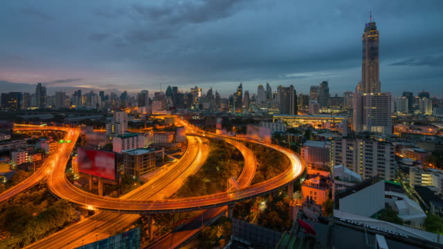 4k time lapse night to day of sunrise scence of bangkok skyline panorama and skyscraper in bangkok city downtown with light trails od car in curve of expressway in bangkok thailand. - bangkok stock videos & royalty-free footage