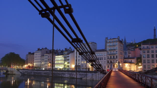 Time Lapse Night to day Track and pan shot of Saone river banks on a footbridge