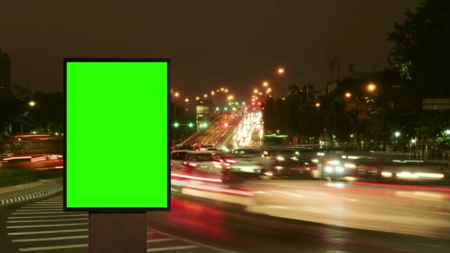 time lapse, night traffic jam with advertising street signs in city. - poster stock videos & royalty-free footage