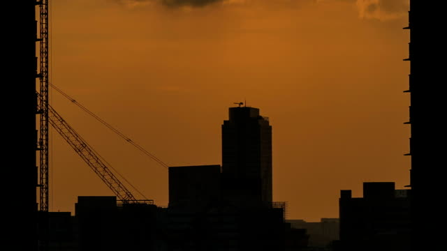 time lapse of a construction site in silhouette - crane stock videos & royalty-free footage