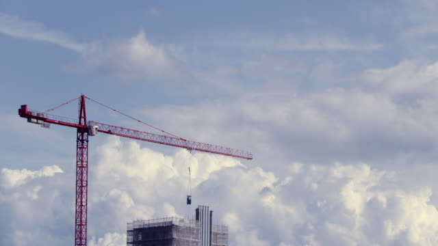 vídeos de stock e filmes b-roll de time lapse of a crane moving against white clouds billowing in a blue sky - data