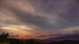 Time lapse of a day to night sequence with clouds moving fast and sun rays glowing onto the high clouds.