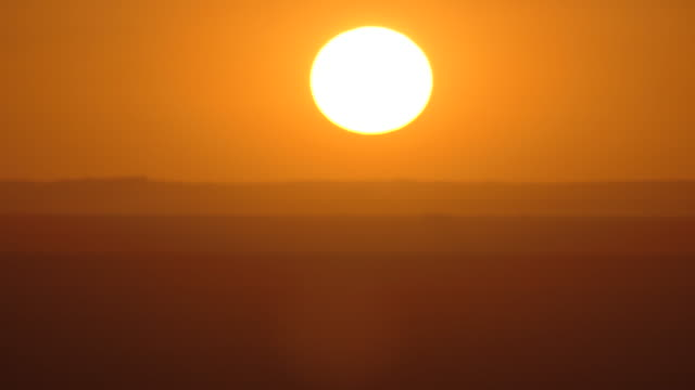 Time lapse of a golden sunset from the top of a mountain overlooking many distant horizonal mountain ranges