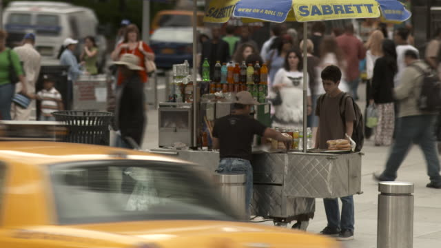 time lapse of a hot dog vendor servicing his guests on a busy corner in new york - hot dog stock videos & royalty-free footage