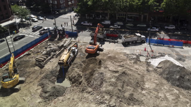 Time lapse of a large hole being dug by two excavators, filled with water by an industrial vacuum truck, then covered by the two excavators at an early stage construction site in an urban setting