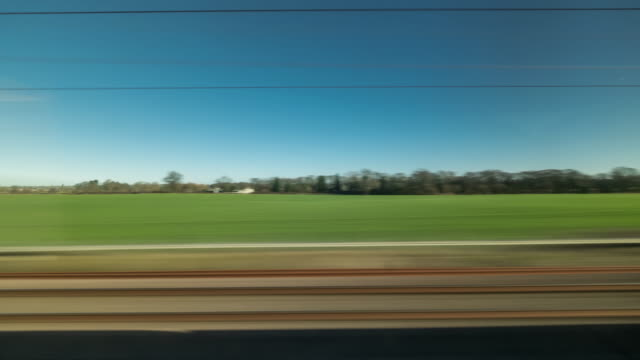 time lapse of a passenger's point of view looking out of a fast moving train window passing through a bright sunny rural landscape and some residential housing with clear blue skies above - passenger point of view stock videos & royalty-free footage