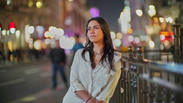 vídeos de stock e filmes b-roll de time lapse of a young woman in the city at night standing still. - esperar