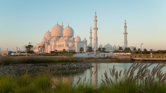 time lapse of abu dhabi grand mosque at dusk, day to night - grand mosque stock videos and b-roll footage