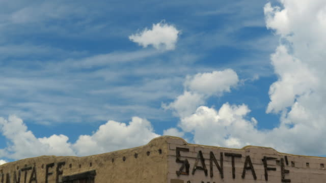 Time lapse of adobe Sa ta Fe building with sign and moving clouds