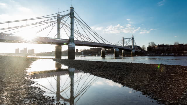 london - circa 2013: time lapse of albert bridge in moviment in low tide and reflection in the water at sunset - low tide stock videos & royalty-free footage