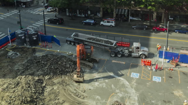 Time lapse of an excavator at an early stage construction site in an urban setting performing a variety of tasks including loading a dump truck with debris