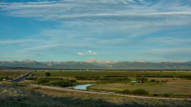 time lapse of an idaho valley with the teton mountain range in the background - zeitraffer tag bis dämmerung stock-videos und b-roll-filmmaterial