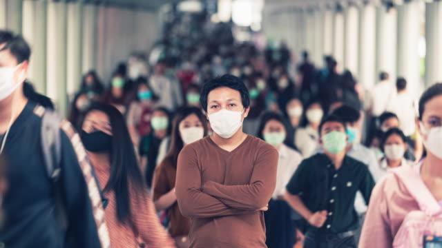 zeitraffer des asiatischen mannes, der eine gesichtsmaske trägt, um coronavirus oder covid-19 ausbruch unter überfüllten menschen zu verhindern - large group of people stock-videos und b-roll-filmmaterial