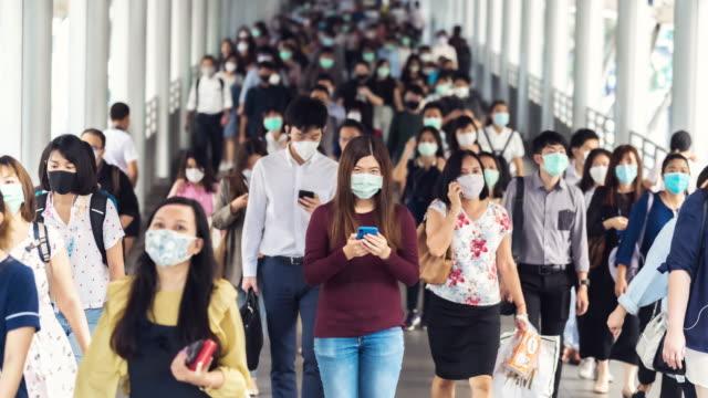 混雑した人々の間でコロナウイルスまたはcovid-19の流行を防ぐためにフェイスマスクを着用したアジアの女性のタイムラプス - 歩行者点の映像素材/bロール