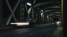 Time lapse of asphalt road under the steel structure of an old metal bridge. Night traffic lights in the tunnel. City life, urban scene, car light trails, transport and traffic concept. Long exposure
