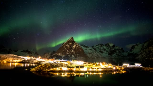 time lapse of aurora borealis dancing on mountains with fishing village - norvegia video stock e b–roll