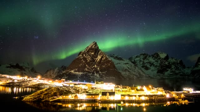 Time lapse of aurora borealis dancing on mountains with fishing village