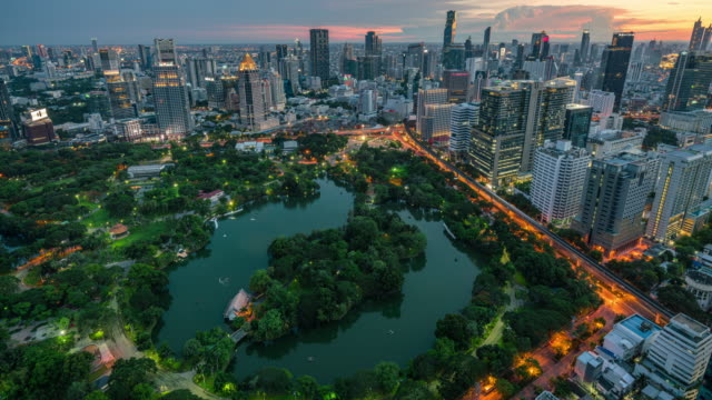 vídeos de stock e filmes b-roll de time lapse of bangkok cityscape and lumpini park green space view, day to night - environmental conservation