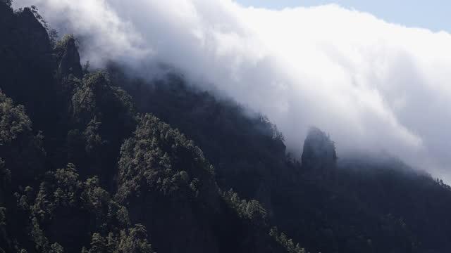 vídeos de stock e filmes b-roll de time lapse of beautiful cascade of clouds crawling in the volcanic landscape in la palma island. cascada de nubes bajando por el paisaje montañoso de la isla de la palma. - espiritualidade
