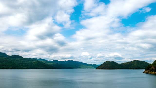 美しい湖と緑の山を背景に曇り空の時間経過