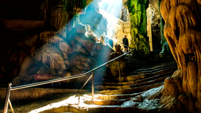 time lapse of beautiful sunlight pass through entrance of cave with people moving - mystery stock videos & royalty-free footage
