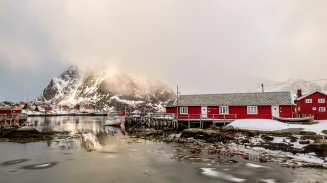 vidéos et rushes de laps de temps de blizzard dans le village de pêcheurs avec la montagne dans l'océan arctique - ensoleillé