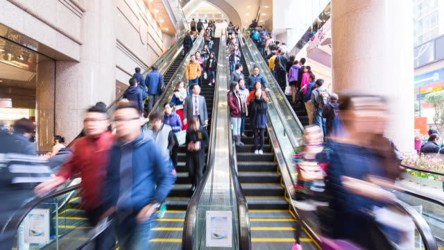 Time Lapse of blurred people moving on escalator, zoom out